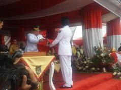 Bupati Rohul H.Sukiman saat memberikan bendera merah putih kepada salah seorang pasukan pengibar bendera di halaman kantor Bupati Rohul, acara berjalan dengan khidmat dan sukses.