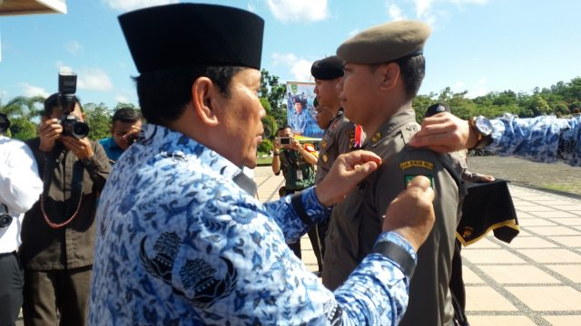 Bupati Sukiman pasangkan pita kepada petugas pengamanan Pilkades serentak gelombang II tahun 2018