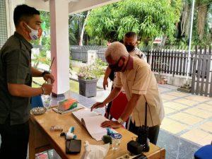 Bupati Asahan H.Surya, B.Sc sedang mengisi buku tamu saat hadir penuhi panggilan Bawaslu Asahan