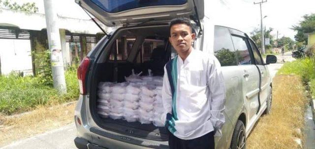 Sekjen GMMA Kab.Asahan, Aris Ardi Sitorus akan membagi kepada masyarakat nasi kotak sedekah dari keluarga alm, H.Taufan Gama Simatupang.